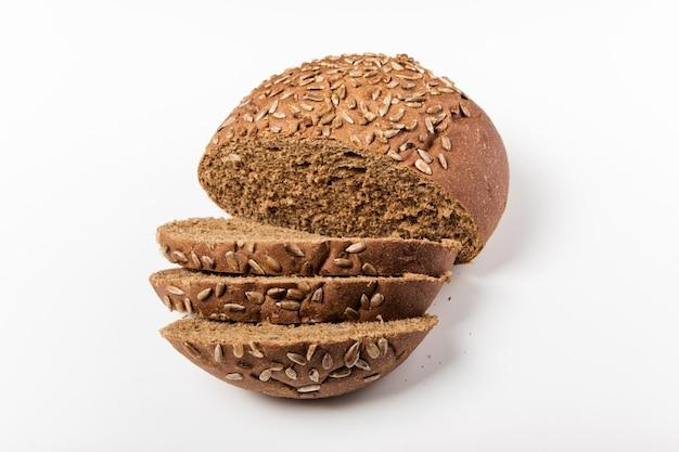 Pain de grains entiers avec des graines tranchées sur la planche à découper en bois.