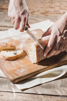 Pain de grains entiers mis sur plaque de bois de cuisine avec un chef tenant un couteau en or pour la coupe.