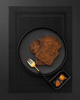 Pain grillé sur une assiette sombre sur un drap noir
