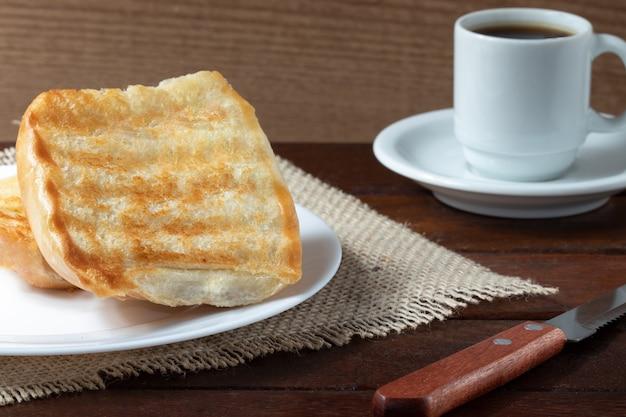 Pain grillé au beurre et café noir, mise au point sélective.