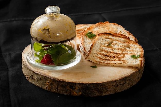 Pain grillé avec une boîte de pâté sur un plateau en bois