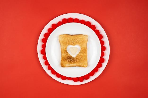 Pain grillé avec une brûlure en forme de cœur sur une table rouge. concept de vacances de la saint-valentin. petit déjeuner festif, déjeuner.
