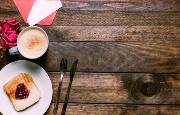 Pain grillé avec de la confiture sur une assiette près d'une tasse de boisson, de fleurs, d'une enveloppe et de couverts
