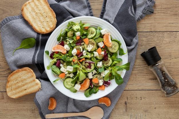 Pain grillé à côté de l'assiette avec salade sur table