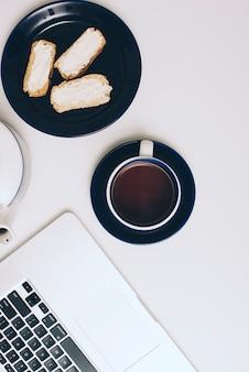 Pain grillé avec du fromage à la crème; tasse à café et ordinateur portable sur fond blanc