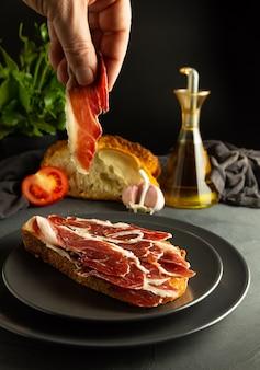 Pain grillé avec du jambon ibérique sur des assiettes noires et un fond rustique, une main tenant une tranche de jambon