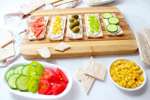 Pain grillé fait maison au fromage cottage et aux olives vertes, tranches de chou, tomates, maïs, poivron vert sur une planche à découper. concept de nourriture saine, vue de dessus. lay plat