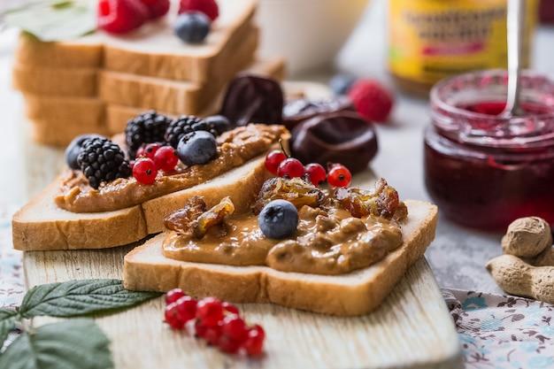 Pain grillé fait maison avec de la confiture et du beurre d'arachide sur table en bois pour le petit déjeuner. délicieux pain grillé prêt à servir. pain grillé avec tartinade pour le petit déjeuner.