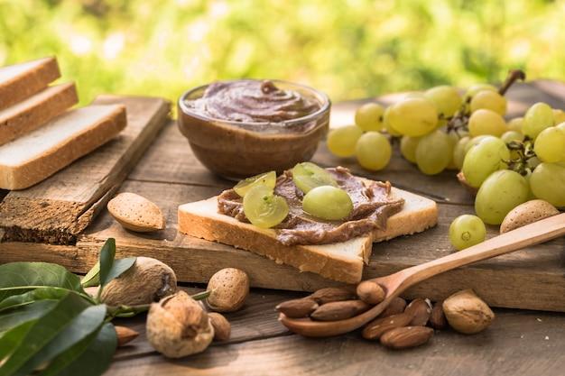Pain grillé fait maison avec du beurre de raisin et d'amande sur la table en bois pour le petit déjeuner. délicieux pain grillé prêt à servir. pain grillé avec tartinade pour le petit déjeuner.