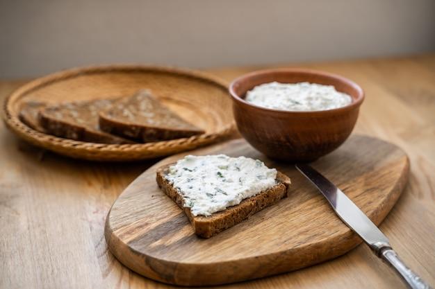 Pain grillé maison avec du fromage cottage et du persil sur planche de bois.
