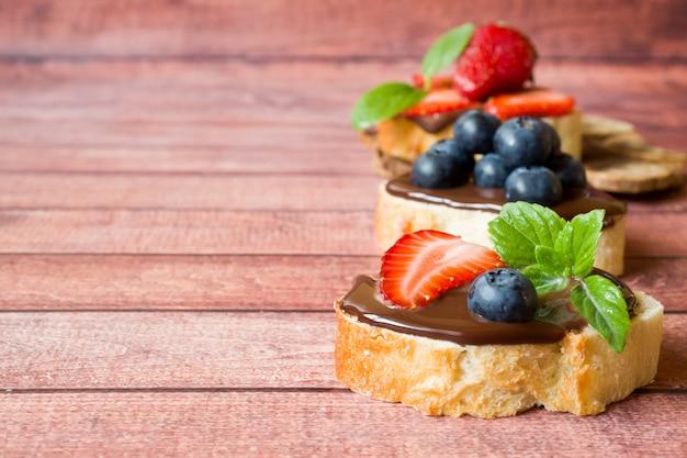 Pain grillé avec pâte de chocolat et fraises myrtilles à la menthe sur la table espace copie