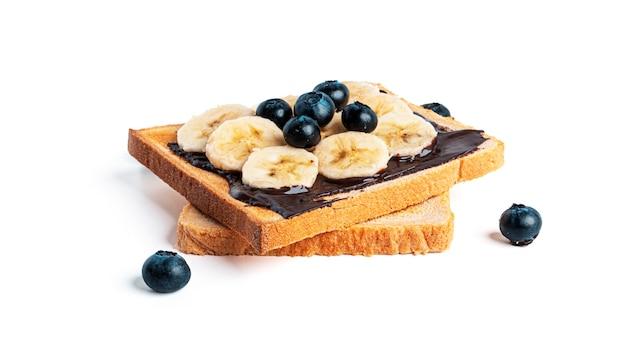 Pain grillé avec pâte à tartiner au chocolat, baies et banane isolé sur blanc.