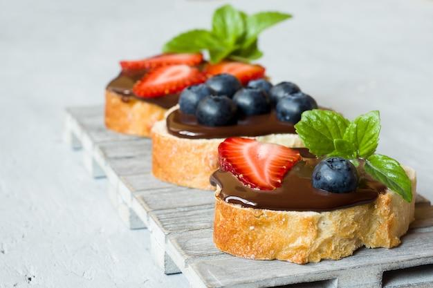 Pain grillé avec pâte à tartiner au chocolat et baies fraises myrtilles à la menthe sur un support en bois gris