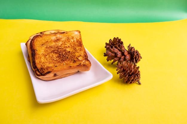 Pain grillé sur une plaque blanche avec des fleurs d'épinette sur un fond de papier jaune et vert. toast pour le petit déjeuner. photo horizontale