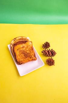 Pain grillé sur une plaque blanche avec des fleurs d'épinette sur un fond de papier jaune et vert. toast pour le petit déjeuner. photo verticale