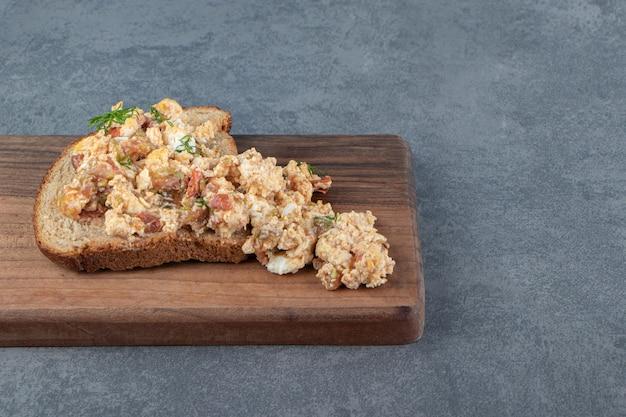 Pain grillé avec salade aux œufs sur planche de bois.