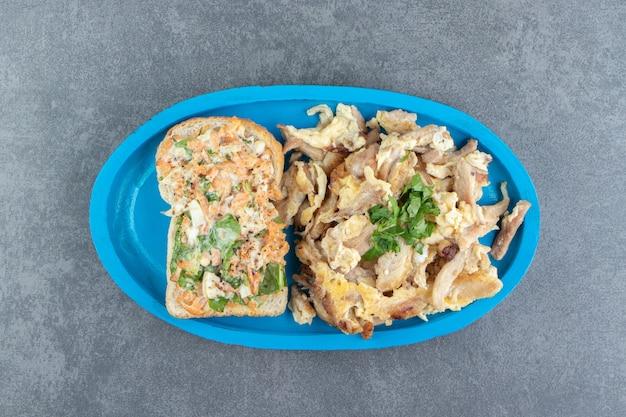 Pain grillé avec salade et oeuf sur plaque bleue.
