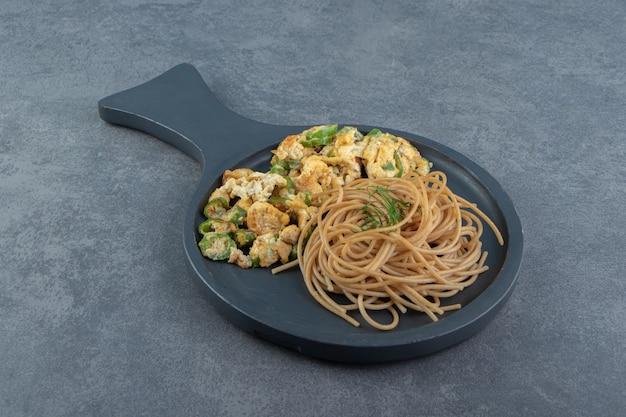 Pain grillé avec salade et spaghetti sur tableau noir.