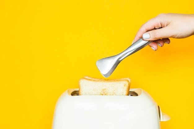 Le pain grillé sort du grille-pain sur un fond jaune