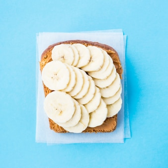 Un pain grillé tartiné de beurre de cacahuète avec des tranches de banane sur un fond bleu
