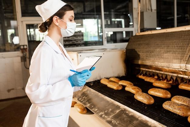 Pain. ligne de production de pain. femme en uniforme. contrôle sanitaire.