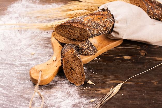 Pain maison au sésame et aux graines de pavot sur une table en bois.