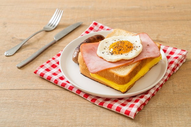Pain maison garni de fromage toasté jambon et œuf frit avec saucisse de porc pour le petit déjeuner