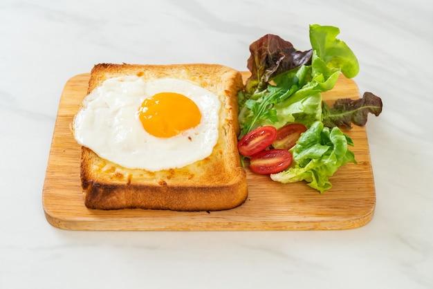 Pain maison grillé avec fromage et œuf frit sur le dessus avec salade de légumes pour le petit déjeuner