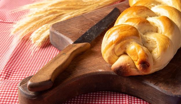Pain maison, pain tressé sur bois et nappe à carreaux rouge et blanc, un couteau et une branche de blé.