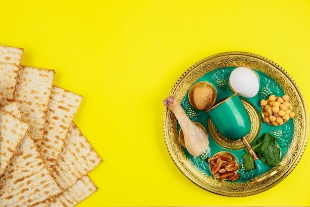 Pain de matsa juif avec coupe en argent et fleurs sur fond rustique en bois.