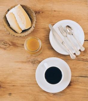 Pain moelleux dans un panier en osier; confiture; tasse à café et des couverts sur une plaque blanche sur un fond en bois