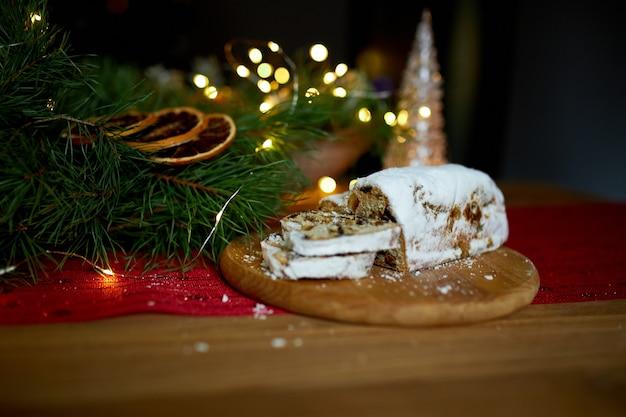 Pain de noël allemand volé, stollen de noël sur fond de bois, dessert traditionnel de pâtisserie festive.