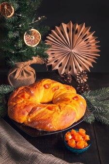 Pain de noël maison cuit au four en forme de guirlande de l'avent de pâte à la levure avec des fruits confits à l'orange sur fond de sapin de noël.