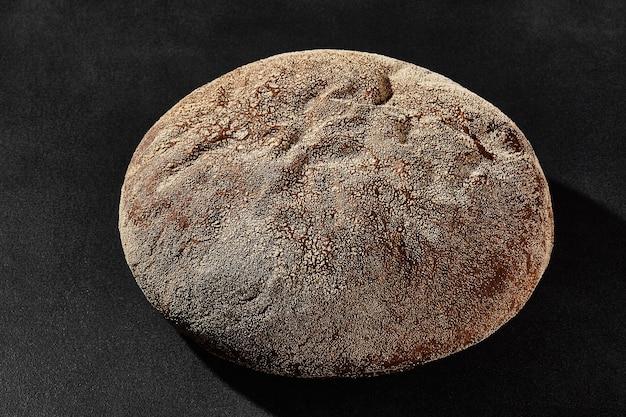 Pain noir rond cuit au four savoureux saupoudré de farine