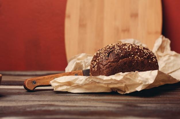 Pain noir de seigle avec un couteau sur un paquet de papier image de texture de table en bois. photo de haute qualité