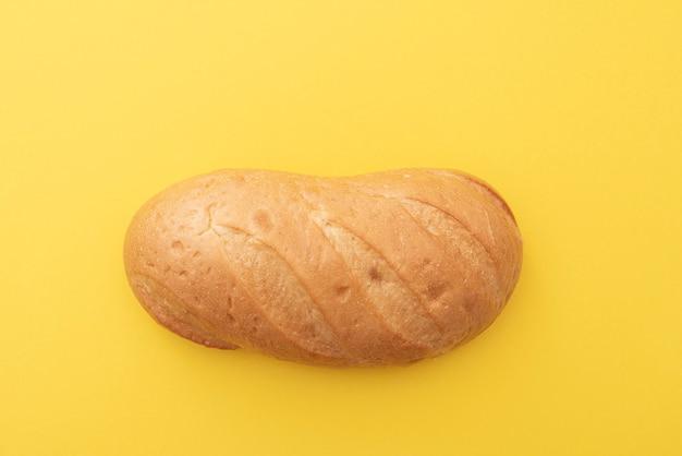 Pain, pain blanc, bâton sur une surface jaune, vue de dessus, mise en page, espace pour le texte