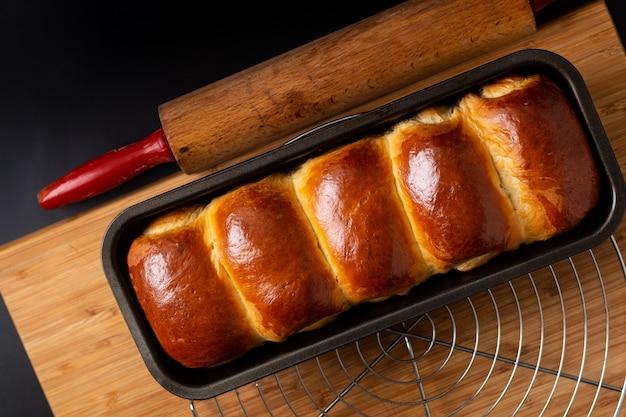 Pain de pain de lait doux fait maison bio cuit au four dans un moule à pain sur une planche en bois avec espace de copie