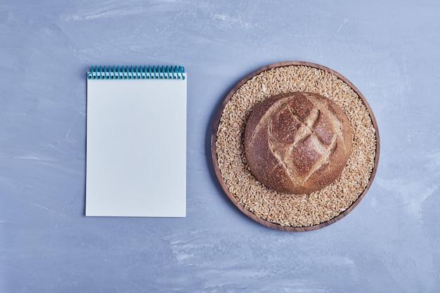 Pain de pain rond fait à la main sur table grise avec un livre de recettes de côté.