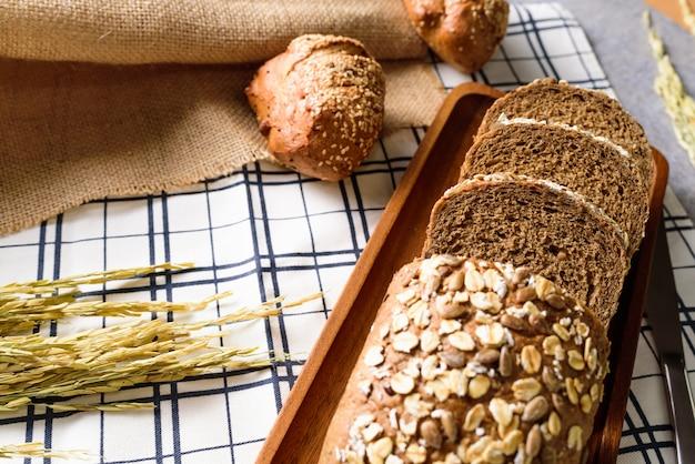 Le pain de pain de seigle de blé entier est coupé et placé sur une plaque de bois.
