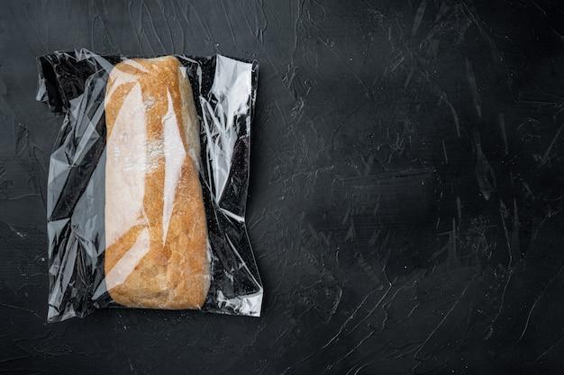 Pain panini ciabatta dans un sac en plastique, sur fond noir, vue de dessus à plat, avec copyspace et espace pour le texte