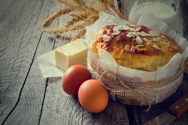 Pain de pâques et ingrédients sur fond de bois rustique