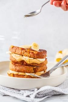Pain perdu au beurre de cacahuète et à la banane sur une assiette blanche.