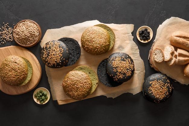 Pain et petits pains végétaliens sans gluten de différents types avec du charbon de bois de spiruline de sarrasin sur fond noir
