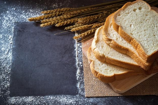 Pain sur une planche à découper en bois et les grains de blé placés à côté