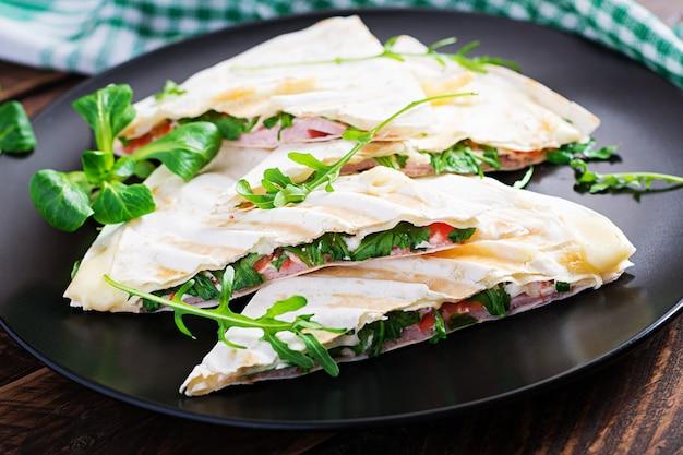 Pain plat fait maison avec jambon, fromage et tomates et herbes vertes