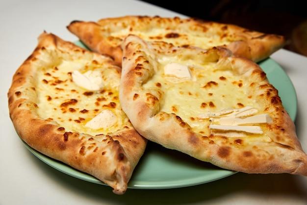 Pain plat traditionnel ajarian khachapuri ou hachapuri avec du fromage et du beurre sur une assiette