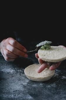 Pain plat traditionnel portugais bolo do caco. mains féminines beurrant le pain. mise au point sélective