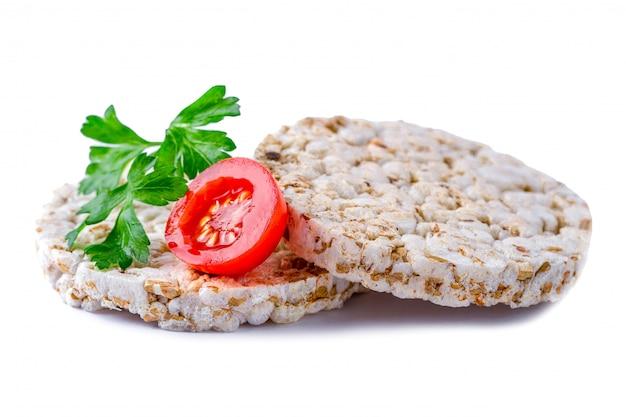 Pain de riz isolé avec des tomates cerises et du persil frais sur fond blanc