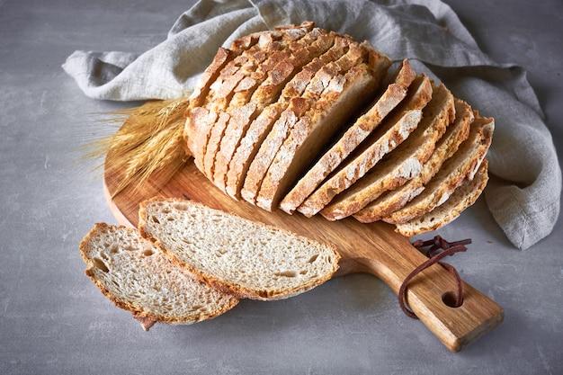Pain rond blanc avec des épis de blé sur une planche à découper en bois sur pierre grise