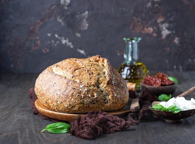 Pain rond de pain au levain fraîchement préparé avec du fromage ricotta, des tomates séchées, du basilic et de l'huile d'olive.